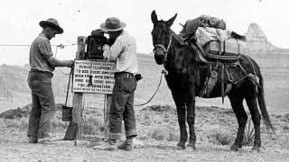 Two park rangers repairing emergency telephone in canyon. Pack mule to their right.