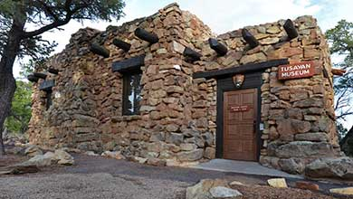 front of Tusayan Museum, a small mostly stone building with log vigas and lentils. NPS Arrowhead above front door.