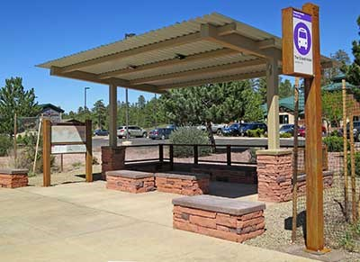 Typical Tusayan shuttle bus stop/shelter have red stone benches beneath a olive color corrugated metal roof. There is also a route map exhibit and an elevated sign on a pole that identifies each stop.