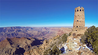 Perched on the rim to the right of Grand Canyon stands the Desert View Watchtower, against a deep blue sky.