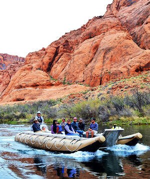 A large motorized raft holding eight people on board is traveling down a river with orange sandstone cliffs in the background, with vegetation along the shoreline.