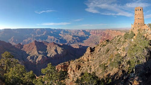 Looking across the vast expanse of Grand Canyon landscape towards a round, stone Watchtower on the far right, perched on the edge of a cliff.