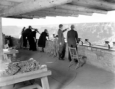 NATURALIST EDWIN MCKEEE SHOWS THE CANYON TO VISITORS FROM THE PARAPET OF YAVAPAI OBSERVATION STATION.
