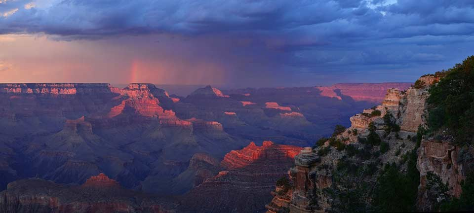 A dramatic red sunset as seen looking east from Yaki Point with stark blue clouds and a trace of a rainbow.