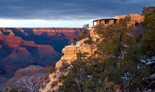A rustic stone building on the edge of a cliff that overlooks colorful cliffs and peaks at sunset.
