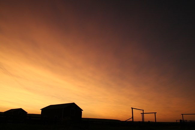 Sunset sky with silhouette of barns and gate arches