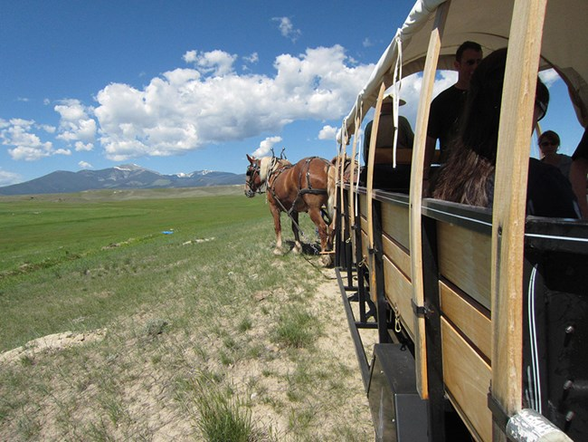 Horse drawn wagon with ranch and mountains in the background