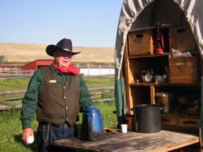 Chuckwagon cook standing by the chuckwagon.