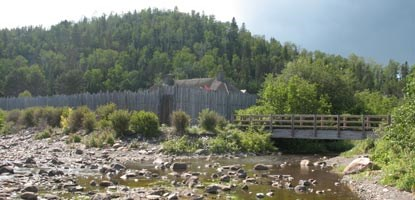 Footbridge across Grand Portage Creek and Great Hall roofline above stockade.