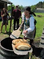 Volunteer places two round loaves of bread on a board.