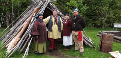 Staff in 18th century clothing stand near birchbark structure.