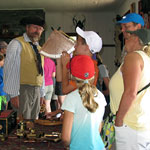 A re-enactor teaches navigation to a family in the great hall.