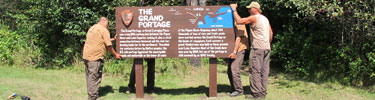 Grand Portage maintenance puts up a routed sign.
