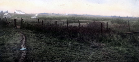 An old photograph of the Grand Portage Trail passing by an overgrown fence in the meadow area.