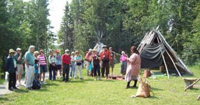 Visitors greeted by interpreter in the Ojibwe Village.