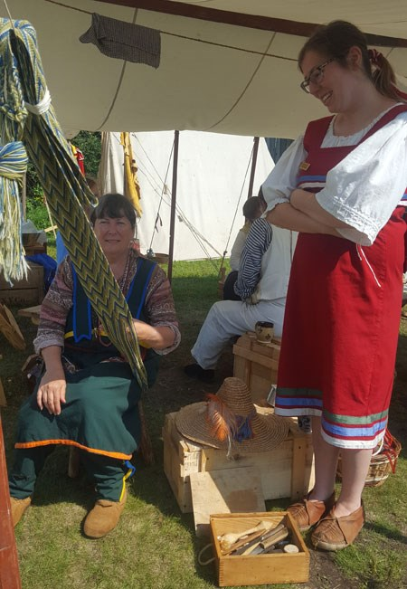 Re-enactors enjoy the finger weaving workshop.