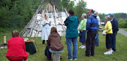 Visitors listen to an interpretive ranger in Grand Portage National Monument's Ojibwe Village.