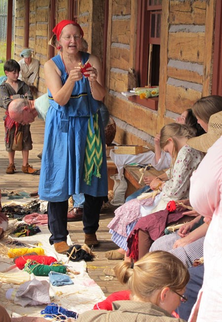 Re-enactor helps participants make dolls.
