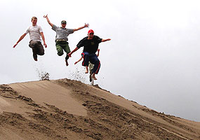 Participants and ranger take a flying leap off a north side dune