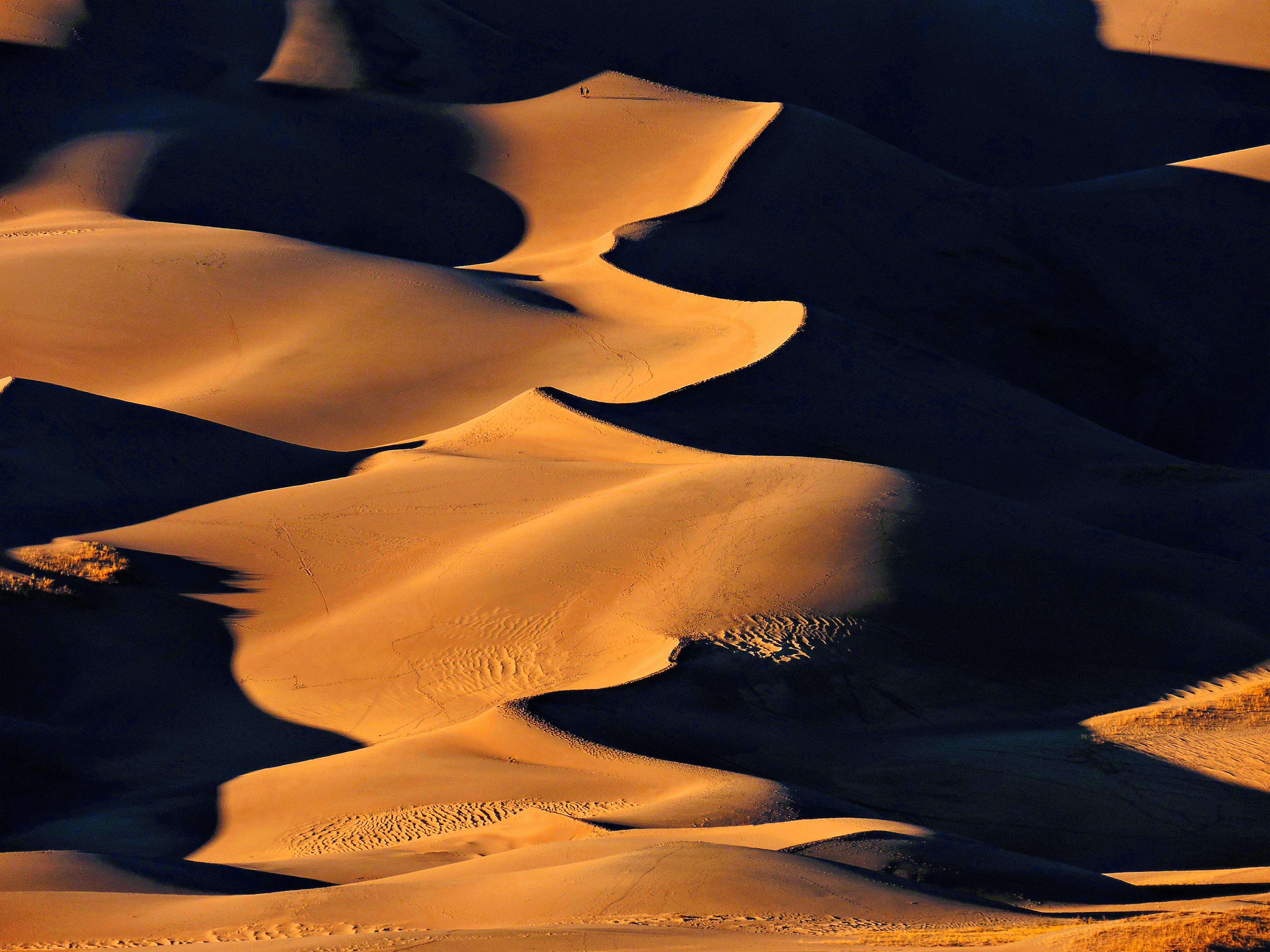 Two people walk on the Great Sand Dunes as shadows cover half the sand.
