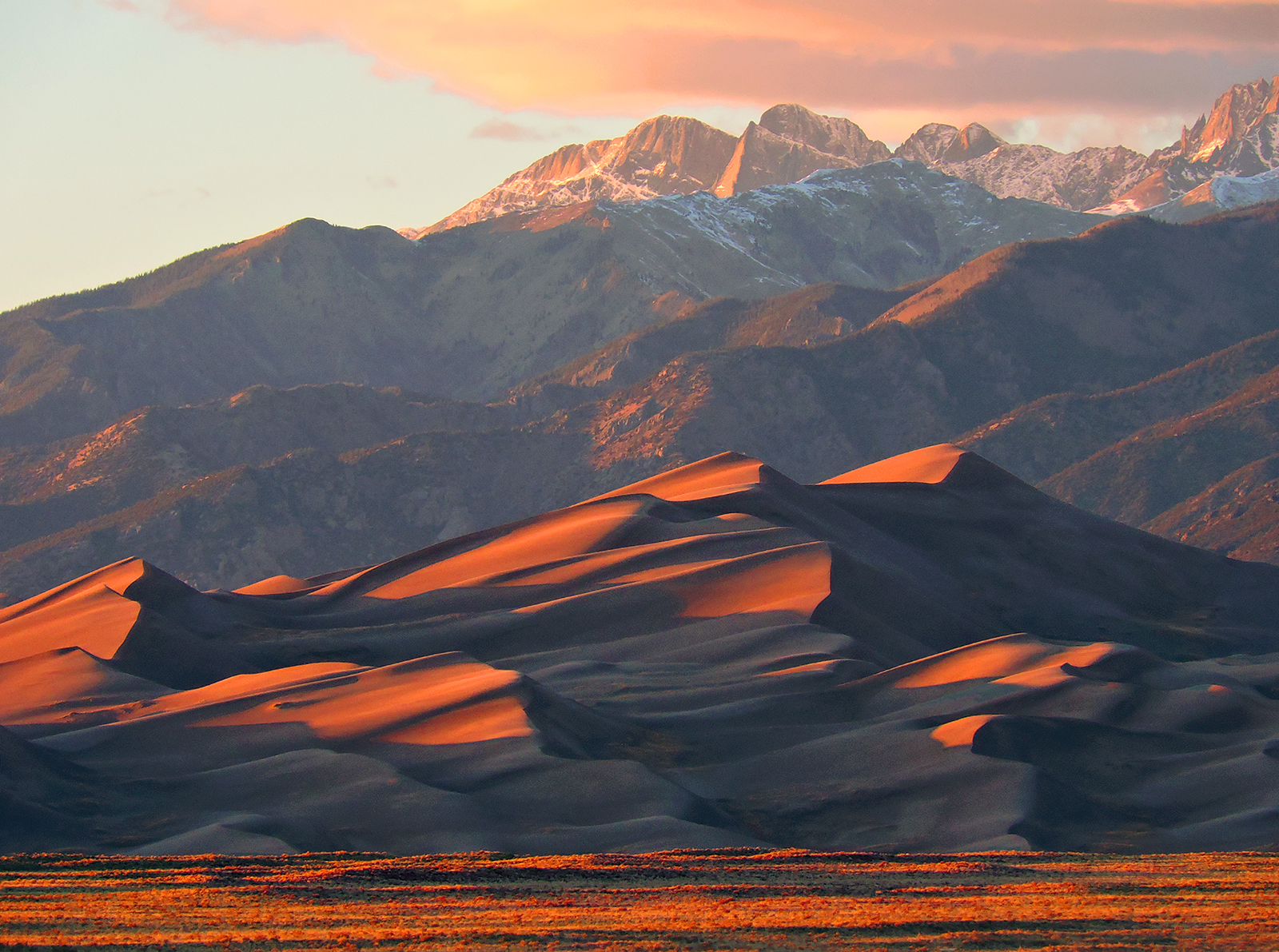 Sunset light on dunes and snow-capped mountain