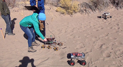 College Girl remotely operating a sand robotic rover