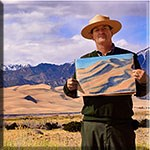 Park ranger holding a color sketch of the dunes, with the dunes and snowcapped mountain in the background