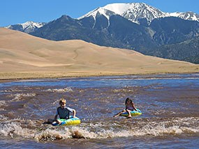 Two children floating Medano Creek with dunes and mountain behind
