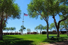 View of Fort Garland Historic Site with adobe buildings and US flag