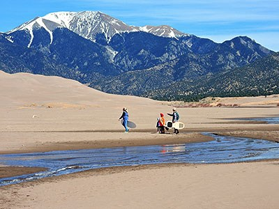Medano Creek at low flow, visitors hiking, dunes, and snowcapped mountain