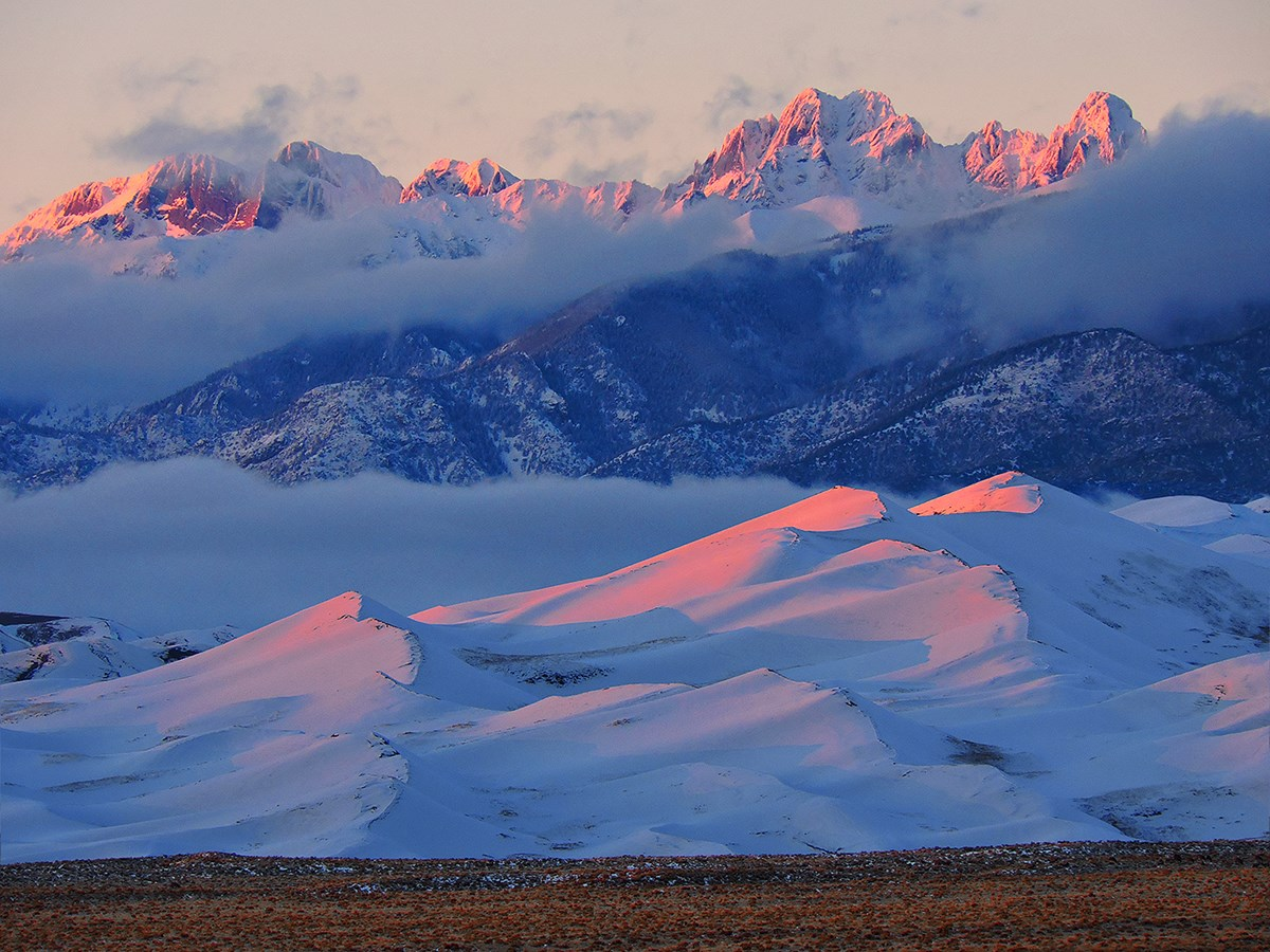 Snow covered Star Dune and Crestone Peaks at Sunset