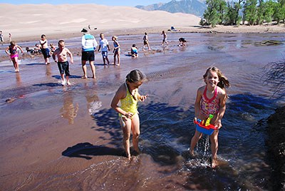 Children and families playing in Medano Creek at low flow