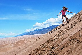 Girl Sandboarding on First Ridge of Dunes