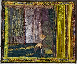 a quilted fabric wall hanging of a tree trunk and leaves