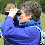 A women with binoculars looks for birds