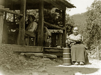 One of the sisters sits in front of a house, churning, and two other sisters are sitting on the porch