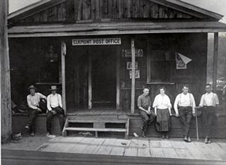 Men standing near the front porch of the Elkmont Post Office and store.