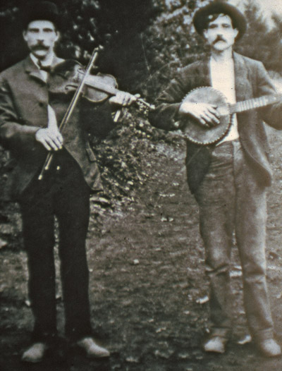 Historic photo of a man with a fiddle standing beside a man with a banjo.