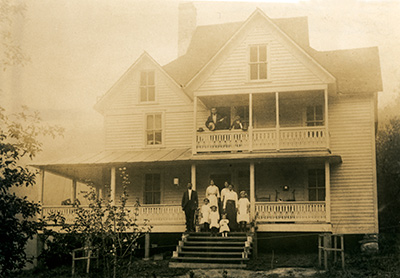 A large family stands on the upper and lower porches of their large Victorian home.