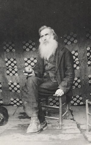 John Walker sits on a wooden chair with an apple in his hand