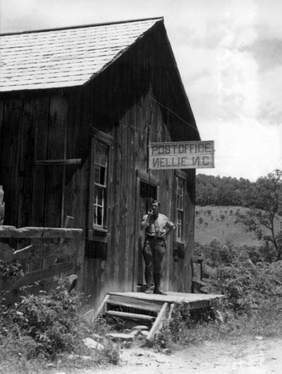 Man standing on the front porch of the Nellie Post Office in Cataloochee.