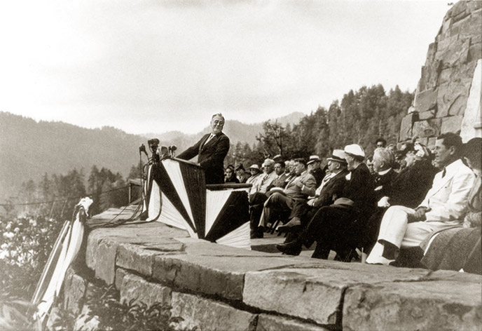 President Franklin Roosevelt stands at the Roosevelt Memorial at the dedication ceremony facing the audience, and a group of people sits behind him.