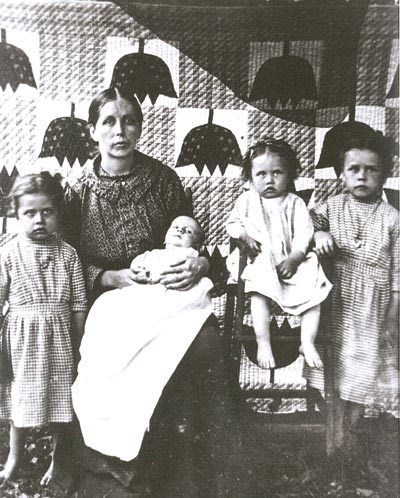 A historic photo of a mountain women posing with her four young children in front of a quilt