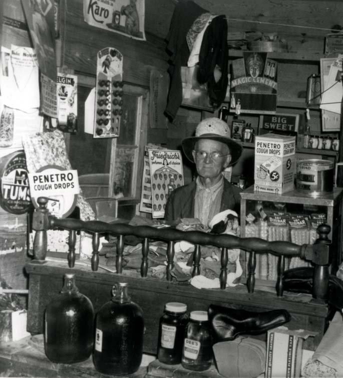Circa 1918 photo of the inside of a general store in Gatlinburg, TN. Store owner behind counter with articles for sale surrounding him on counters and walls.
