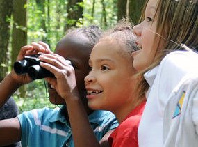 Three young girls use a pair of binoculars to explore the park.