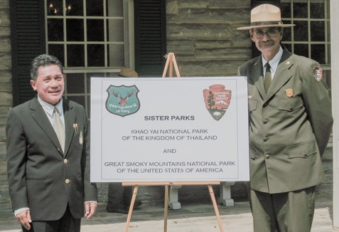 Superintendents of Great Smoky Mountains and Khao Yai National Parks pose for a picture with a sign representing both parks.