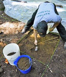 Heath Bailey carefully scrapes away soil layers in an excavation unit.