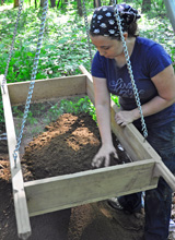 Sifting soil for archeological artifacts.