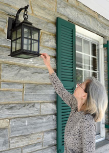 Cultural resources manager Dianne Flaugh indicates a restored historic light fixture in front of the park headquarters building.
