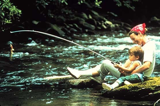 A photograph of a mother and son fishing a park stream.  A fish is hooked on the line of the fishing pole.
